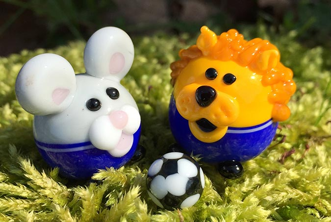 Small glass mouse and lion playing football